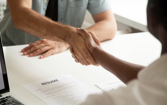 Two hands shaking over a tabletop, paper with RESUME on table between them