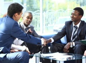 Three men in suits sitting at a glasstop table, two of them shaking hands and smiling, business concluded