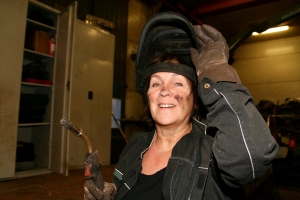 Woman with welding torch and gloves, welding mask tilted up, smiling at camera