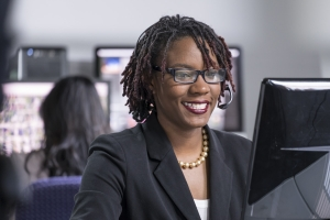 Closeup of woman in formal office attire, looking at computer screen, smiling
