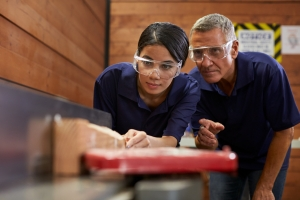 Young woman and older man with safety glasses testing something