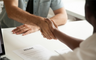 Two people shaking hands over a desk with a resume on it