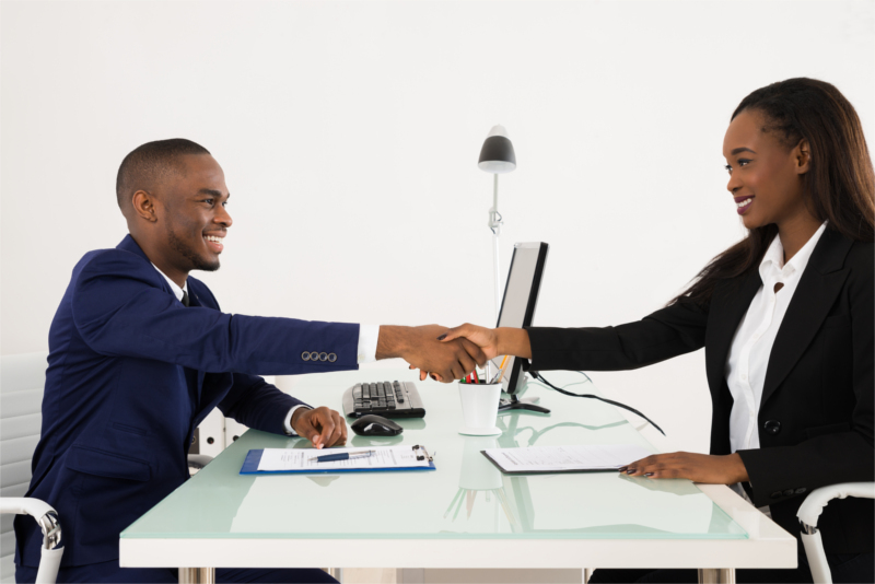 Man and woman, smiling and shaking hands over a desk