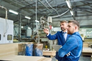 Two men in factory in discussion, looking at something off-camera