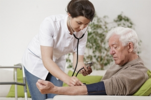 Nurse with stethoscope checking white-haired man's heart rate
