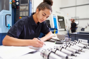 Woman in high-tech factory filling out paperwork, bank of brand-new microphones in front of her